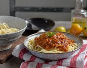 Bowl of spaghetti noodles with tomato sauce and herb garnish