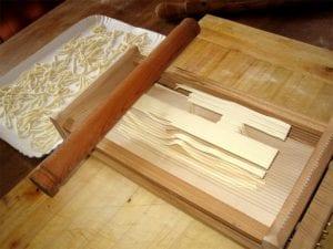 Fresh spaghetti alla chitarra noodles being made on a chitarra