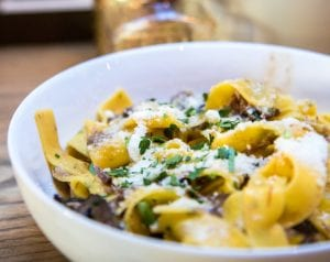 Bowl of tagliatelle pasta in with bits of meat, grated cheese, and bits of herbs as garnish