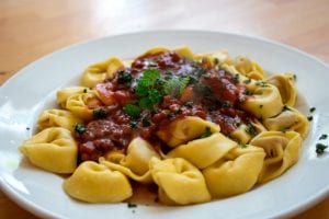 Tortellini pasta in red sauce with bits of ingredients, and garnished with herbs