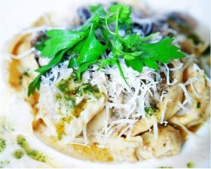 a close up view of tortellini pasta topped with grated cheese and parsley