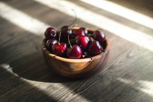 Bowl of cherries on a wooden surface