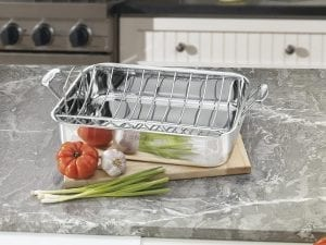 Stainless steel roasting pan with U-shaped rack on a kitchen counter