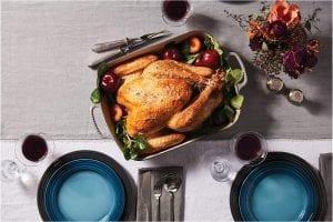 Dinner spread with roast turkey in an enamel roasting pan