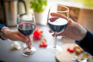 Hands of two people each holding a glass of red wine