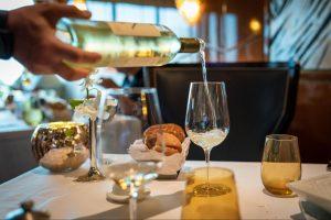 Person pouring white wine into a wine glass