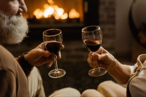 Two people each holding a glass of red wine