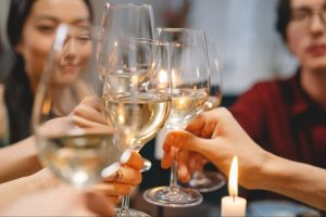 Group of people toasting with glasses of white wine