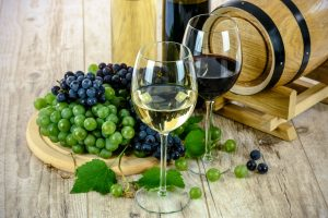 Glasses of white wine and red wine with grapes and a wooden barrel