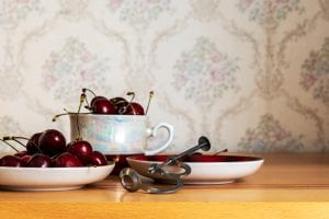 Metal cherry pitter, with cherries on plates