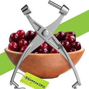 Cherry Pitter Olive and Cherry Pitting Tool, with a bowl of cherries in a wooden bowl