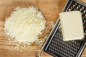 top view of grated mozzarella cheese, slab of cheese, and metal cheese grater