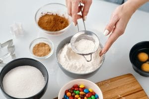 Person straining flour into a small bowl, bowls of baking ingredients