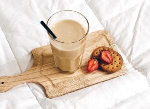 Glass of horchata, with biscuits and sliced strawberries on a wooden board