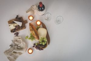 Wine opener, wine, bread, grapes, cheeses, and candles