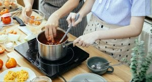 Two people cooking sauce in a saucepan over an induction cooker
