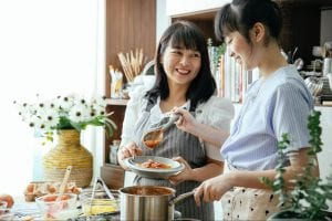 Two women scooping sauce from a metal saucepan to a shallow bowl