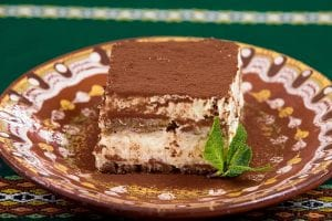 A slice of tiramisu on a plate, garnished with a sprig of mint