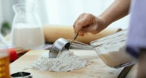 Person scooping flour onto a wooden board