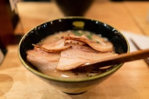 Pieces of chashu or thin pork slices on a bowl of ramen
