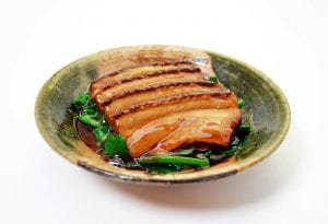 Kakuni or square simmered pork belly on a plate with greens and sauce